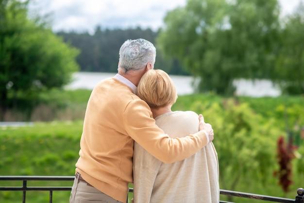Achteraanzicht van een liefhebbende grijsharige echtgenoot die zijn blonde vrouwelijke echtgenoot tegen zijn borst drukt