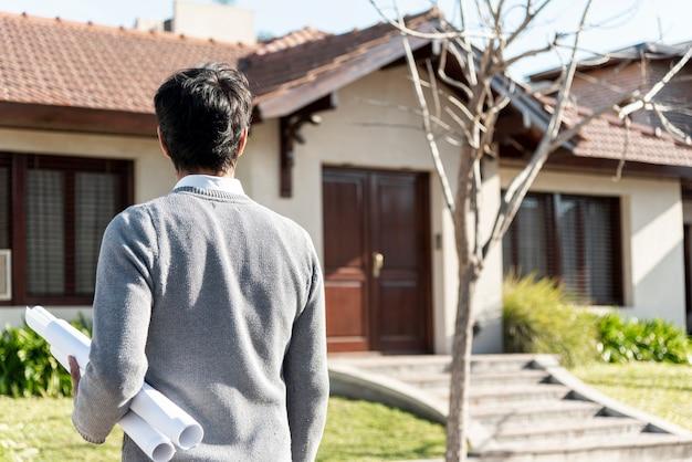 Achteraanzicht van een man die naar een huis kijkt