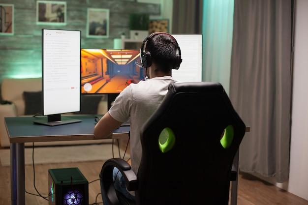 Achteraanzicht van een man die op een gamingstoel zit en 's nachts schietspel speelt. neonlicht in de kamer.