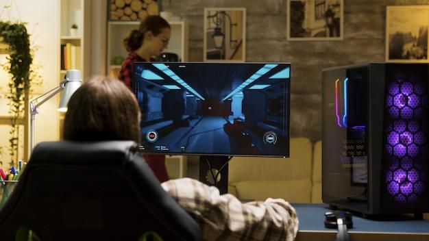 Achteraanzicht van een man die op een gamingstoel zit en spelletjes speelt op de computer. vriendin leest een boek op de achtergrond.