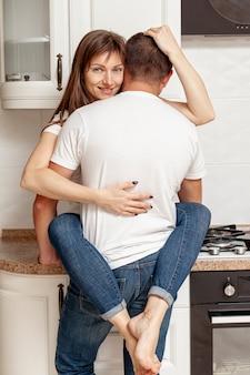 Achteraanzicht van een man die zijn vriendin knuffelt