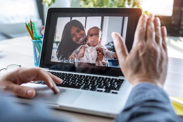 Achteraanzicht van een man die zwaait en spreekt tijdens een videogesprek met zijn vrouw en babydochter op laptop op kantoor.