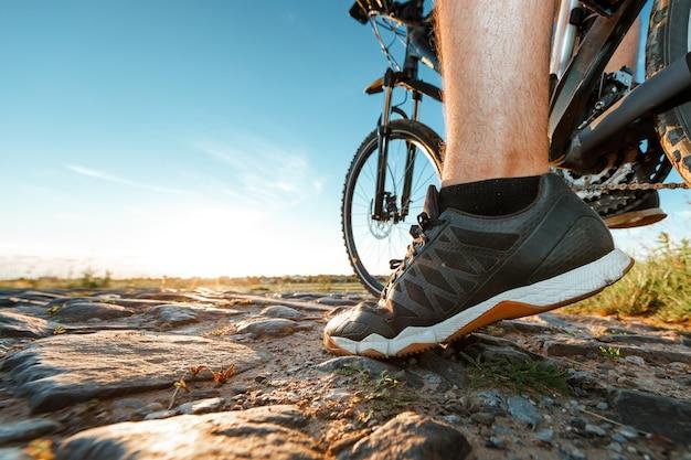 Achteraanzicht van een man met een fiets tegen de blauwe hemel. fietser rijdt op een fiets.