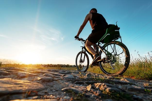 Achteraanzicht van een man met een fiets tegen de blauwe hemel.