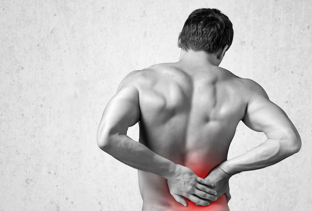 Achteraanzicht van een man zonder shirt die zijn pijnlijke rug aanraakt