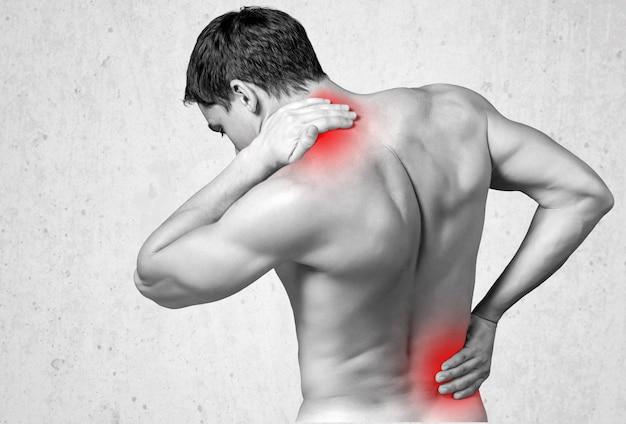 Achteraanzicht van een man zonder shirt die zijn pijnlijke rug en nek aanraakt