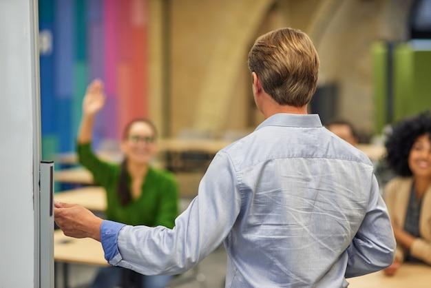 Achteraanzicht van een mannelijke coach of spreker die wijst op het geven van een presentatie aan het publiek