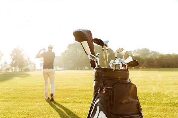 Achteraanzicht van een mannelijke golfspeler swingende golfclub