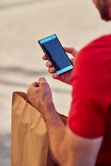 Achteraanzicht van een mannelijke koerier die een mobiele app gebruikt terwijl hij een papieren eco-tas levert met