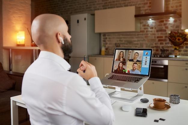 Achteraanzicht van een mannelijke werknemer die op afstand werkt aan een zakelijke videoconferentie op een laptop thuis.