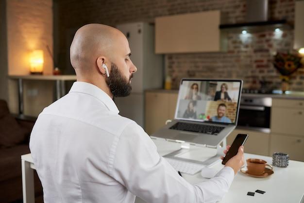 Achteraanzicht van een mannelijke werknemer die op afstand werkt met een telefoon tijdens een zakelijke videoconferentie op een laptop thuis.