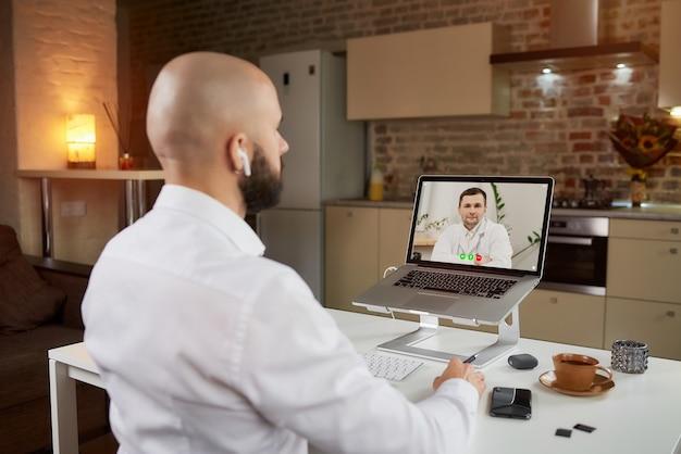Achteraanzicht van een mannelijke werknemer in oortelefoons die naar een arts op een videoconferentie op een laptop luistert.