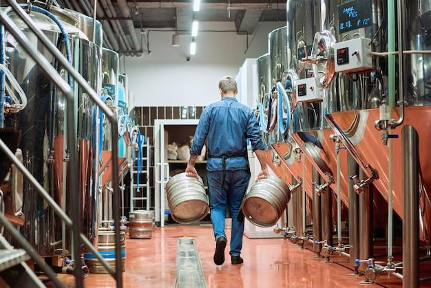 Achteraanzicht van een mannelijke werknemer van een hedendaagse bierfabriek die twee stortbakken draagt terwijl hij langs rijen enorme stalen tanks beweegt