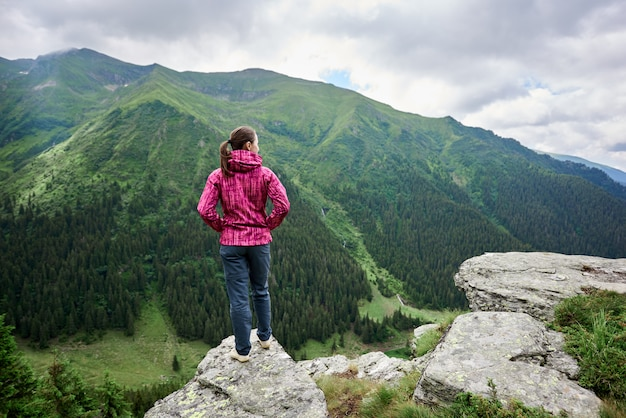 Achteraanzicht van een meisje dat op een klif voor haar staat en een betoverend landschap van machtige groene bergen en wolken boven hen opent