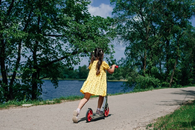 Achteraanzicht van een meisje dat op een scooter rijdt op een pad langs een rivier met bomen groen gras op een zomerdag...