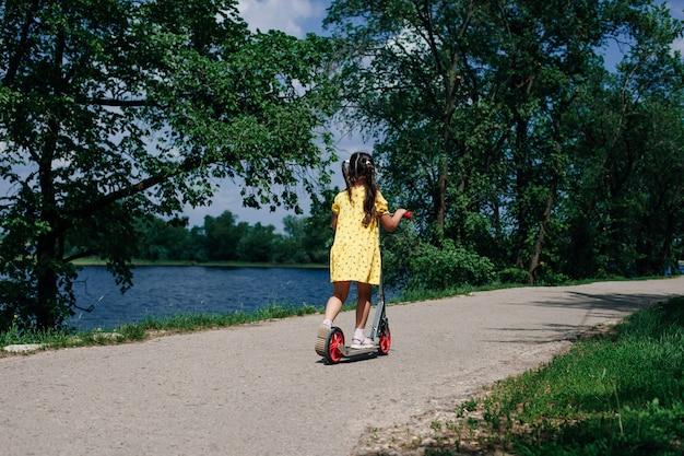 Achteraanzicht van een meisje in een gele jurk die op een scooter rijdt langs een rivier met blauw water in de natuur met ...