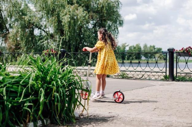 Achteraanzicht van een meisje in een gele jurk die op een scooter rijdt op een pad met groene bloembedden een meisje leert...