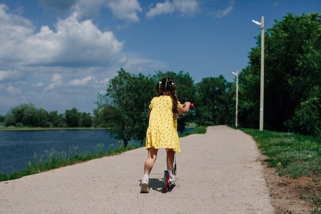Achteraanzicht van een meisje in een gele jurk een meisje leert scooter rijden in een natuurpark bij het meer