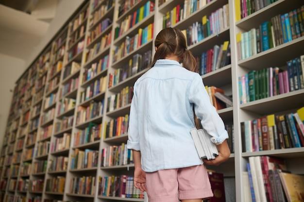 Achteraanzicht van een meisje met paardenstaarten gekleed in vrijetijdskleding die voor de boekenplanken staat