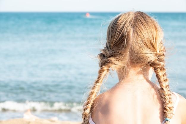 Achteraanzicht van een meisje met staartjes op het strand in de zomer