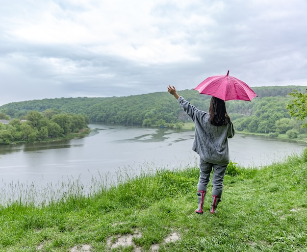 Achteraanzicht van een meisje onder een paraplu tijdens een wandeling in het bos bij het meer bij regenachtig weer