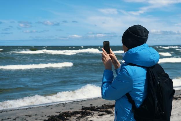 Achteraanzicht van een meisjestoerist die een foto neemt met een digitale camera van een mobiele telefoon, die voor de zee met golven staat