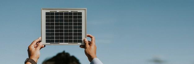 Achteraanzicht van een milieuvriendelijke vrouw die een zonnepaneel in de lucht houdt