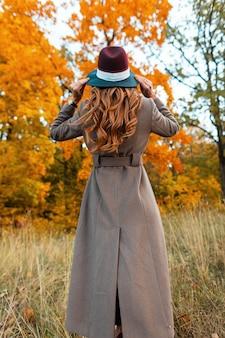 Achteraanzicht van een modieuze jonge vrouw in een stijlvolle lange jas in een elegante hoed met een trendy kapsel in een herfstpark tussen bomen met oranje gebladerte. modern meisje loopt door het bos.