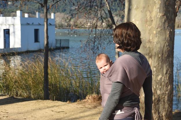 Achteraanzicht van een moeder die oefent om haar zoon naar buiten te dragen