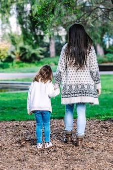 Achteraanzicht van een moeder met haar baby wandelen in een herfst park