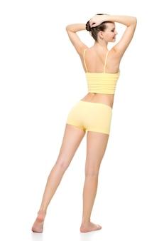 Achteraanzicht van een mooi sportief vrouwelijk lichaam in geel ondergoed poseren geïsoleerd op een witte muur