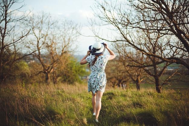 Achteraanzicht van een mooie jonge vrouw in blauwe jurk bedrijf hoed lopen wandelen in de tuin. mooi meisje genieten van een tuin in het vroege voorjaar, buiten ontspannen, plezier maken.