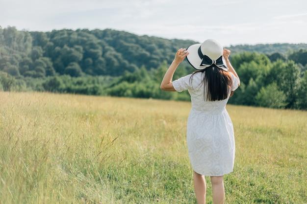 Achteraanzicht van een mooie jonge vrouw in witte jurk met strohoed die op het saliebloemveld loopt