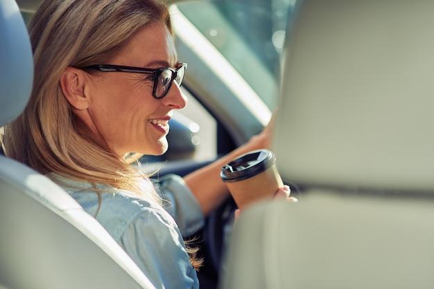 Achteraanzicht van een mooie zakenvrouw van middelbare leeftijd die een bril draagt en achter het stuur zit