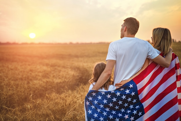 Achteraanzicht van een onherkenbaar gelukkige familie in een tarweveld met amerikaanse vlag