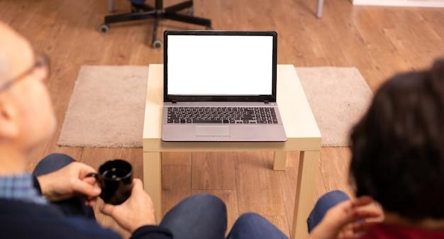 Achteraanzicht van een oud stel in hun woonkamer op zoek naar een laptop met een wit geïsoleerd model.