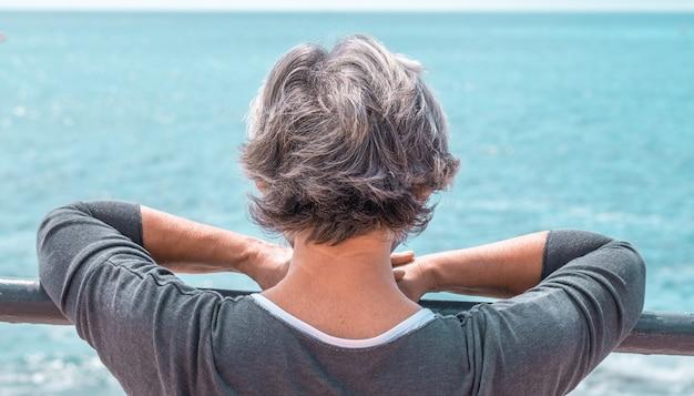 Achteraanzicht van een oudere vrouw die naar zee kijkt