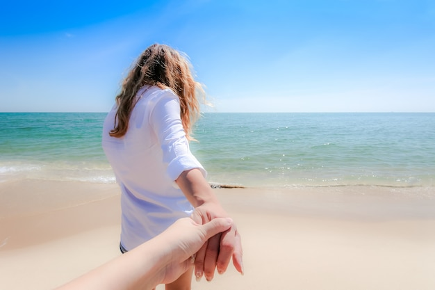 Achteraanzicht van een paar een wandeling hand in hand op het strand te nemen