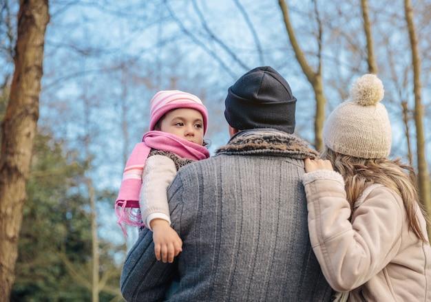 Achteraanzicht van een paar met haar dochtertje dat samen geniet van het boslandschap. familie vrije tijd concept.