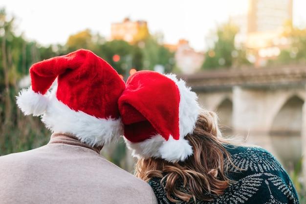 Achteraanzicht van een paar met kerstmutsen op kerstmis 2021. concept van reünie en terugkeer naar huis.