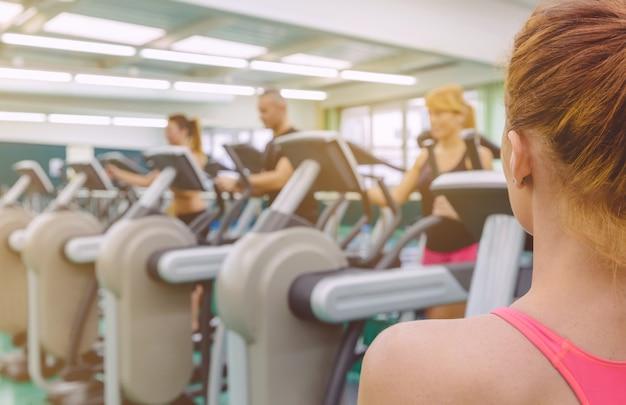 Achteraanzicht van een persoonlijke vrouwelijke coach die naar een groep mensen kijkt in een elliptische trainersessie in het fitnesscentrum