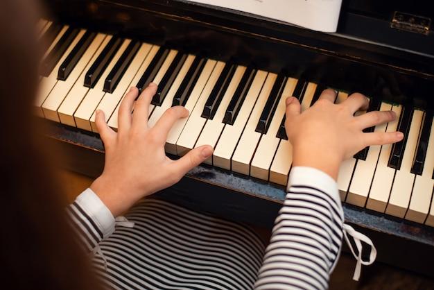 Achteraanzicht van een pianist meisje piano spelen