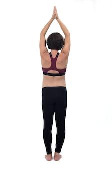 Achteraanzicht van een portret van een zwangere vrouw die traint op een witte achtergrond met uitgestrekte armen