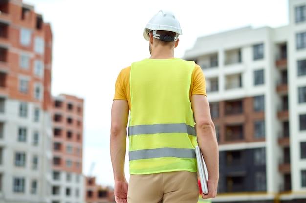Achteraanzicht van een professionele ingenieur met een laptop in zijn hand die een nieuw bouwobject inspecteert