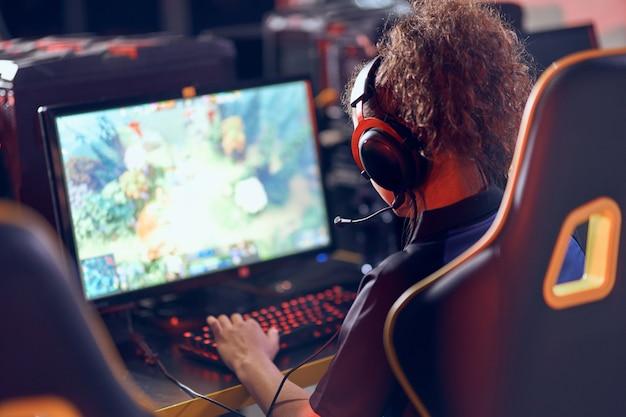 Achteraanzicht van een professionele vrouwelijke cybersport-gamer die een koptelefoon draagt die online videogames speelt
