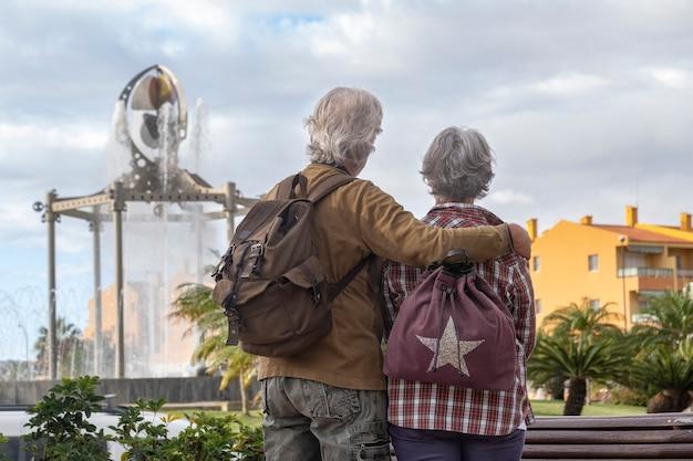 Achteraanzicht van een senior koppel met witte en grijze haren en rugzakken die naar de fontein kijken