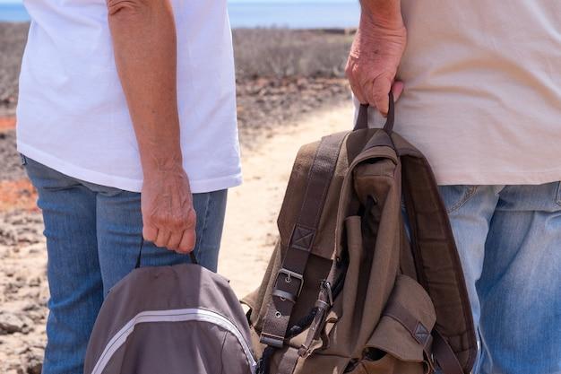 Achteraanzicht van een senior paar reizigers die hun rugzakken vasthouden en genieten van een excursie in de buitenlucht. horizon over zee en zonnige dag