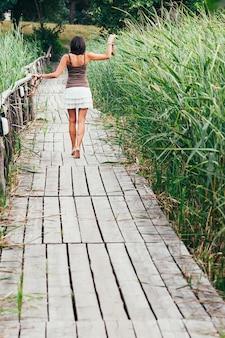 Achteraanzicht van een slank meisje op blote voeten, hoge hakken in handen