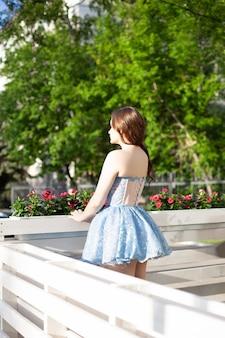 Achteraanzicht van een slanke vrouw in een blauwe korte jurk met een volle rok aan de witte houten ra...