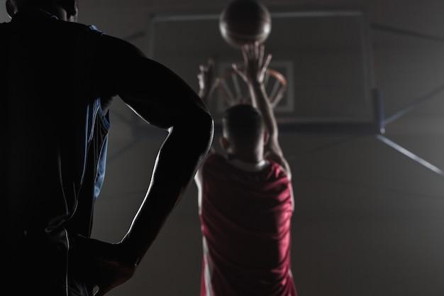Achteraanzicht van een speler die een basketbal schiet